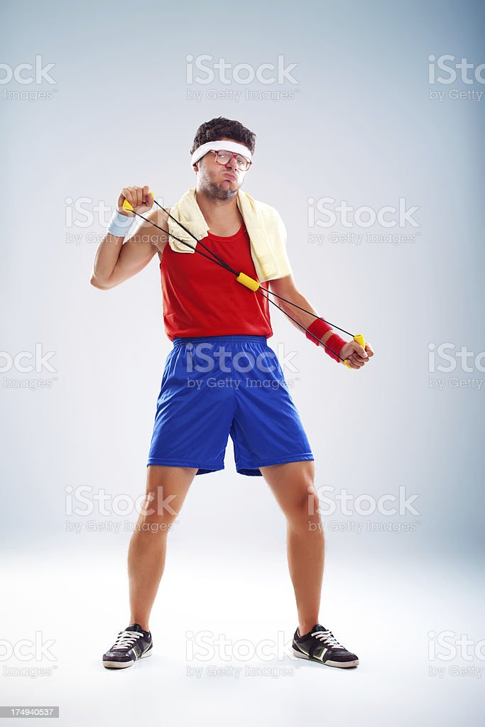 Clumsy fitness man with glasses exercising with resistance band stock photo