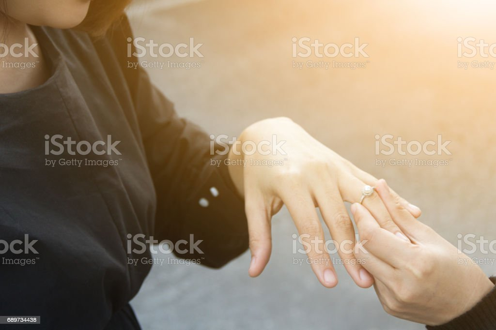 cluseup of bride putting a wedding ring to finger stock photo