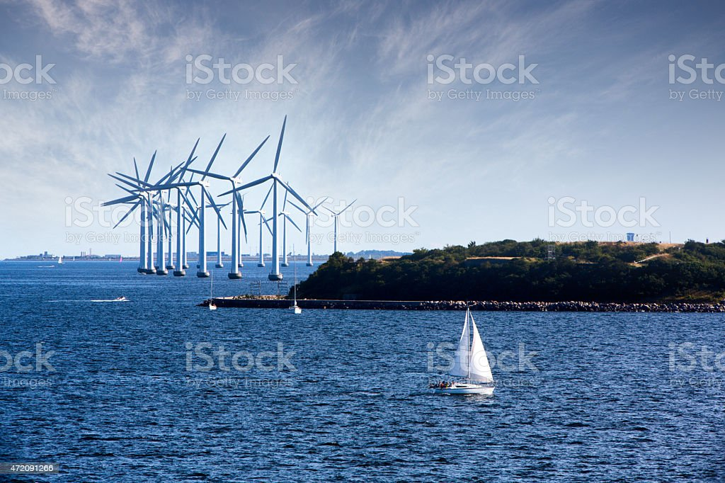 Cluster of Ocean Wind Turbines with Sailboat in Foreground stock photo