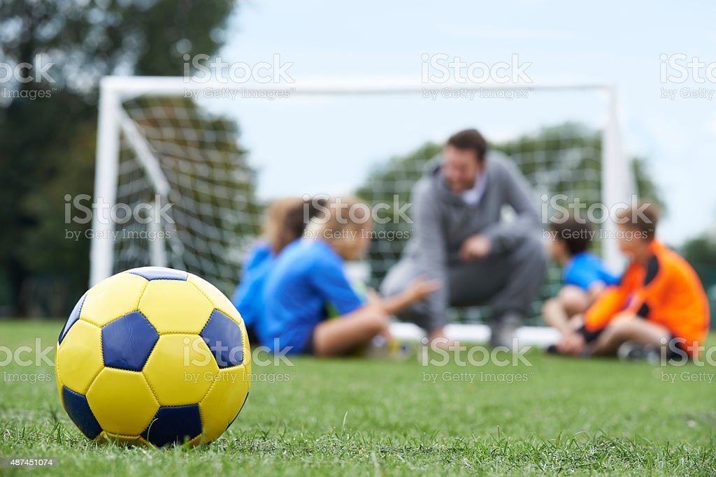 Coach  And Team Discussing Soccer Tactics With Ball In Foregroun stock photo