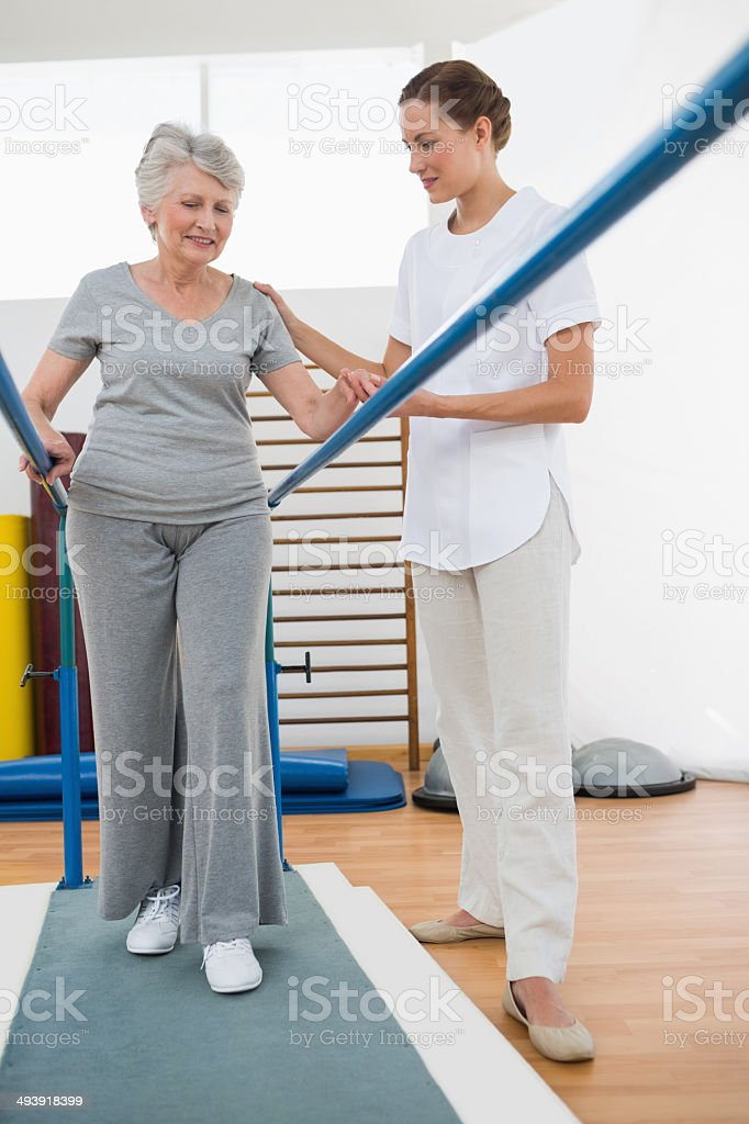 Coach assisting senior woman walking on parallel bars stock photo