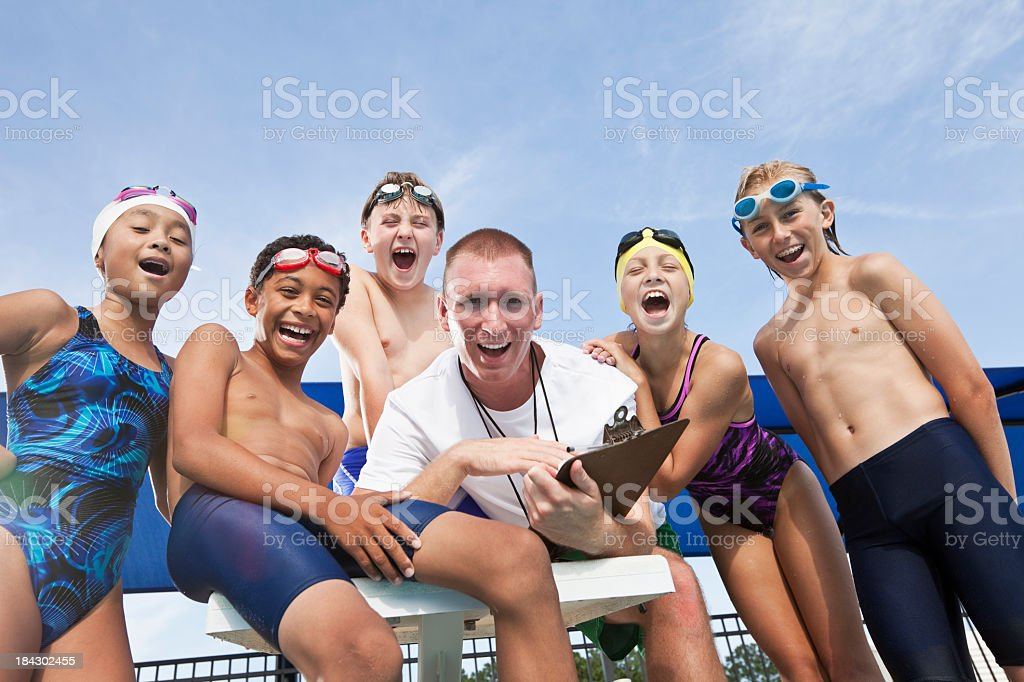 Coach cheering with young swimmers stock photo