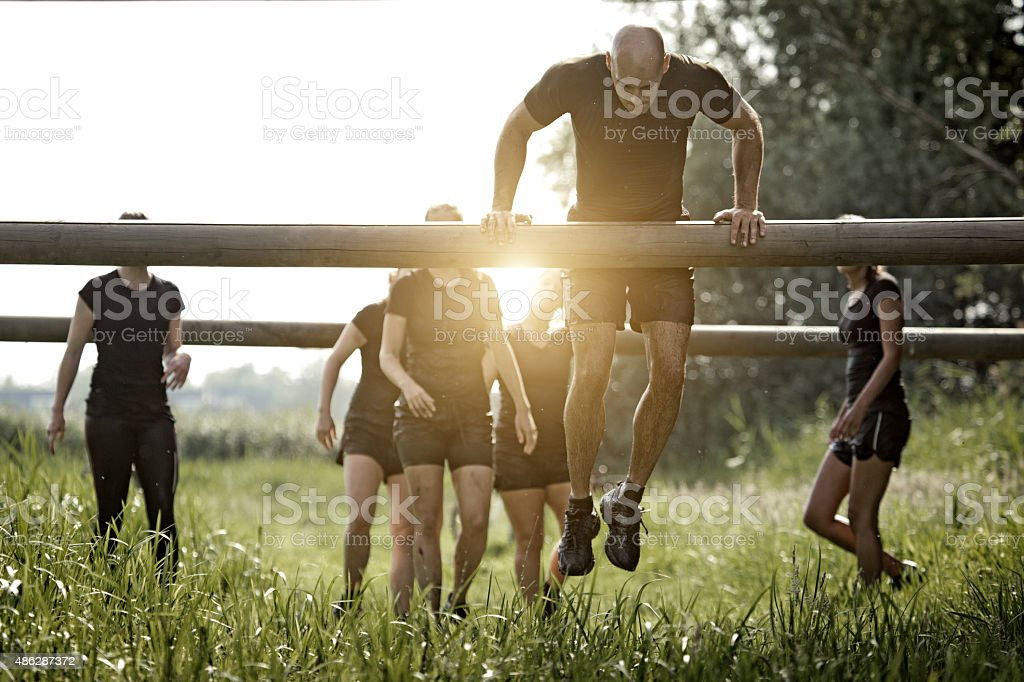 coach demonstrating to group of women how to cross obstacle stock photo
