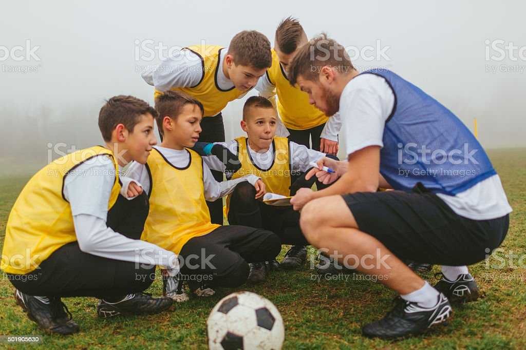 Coach Explaining Strategy To His Kids Soccer Team. stock photo