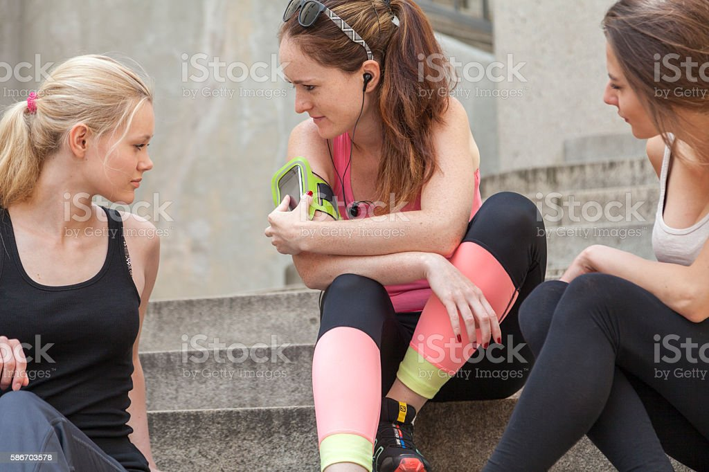 coach explains a running app to her clients stock photo