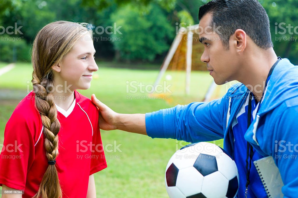 Coach gives teen soccer player pep talk stock photo