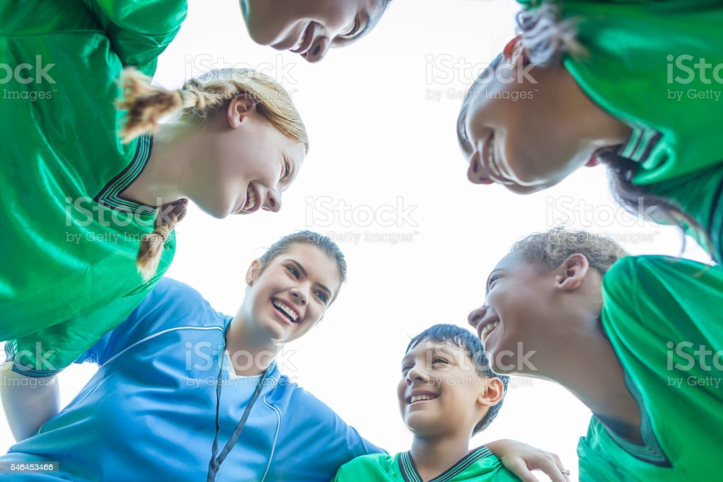Coach gives youth soccer team pep talk stock photo