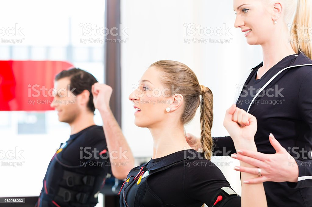 Coach giving ems training to couple stock photo