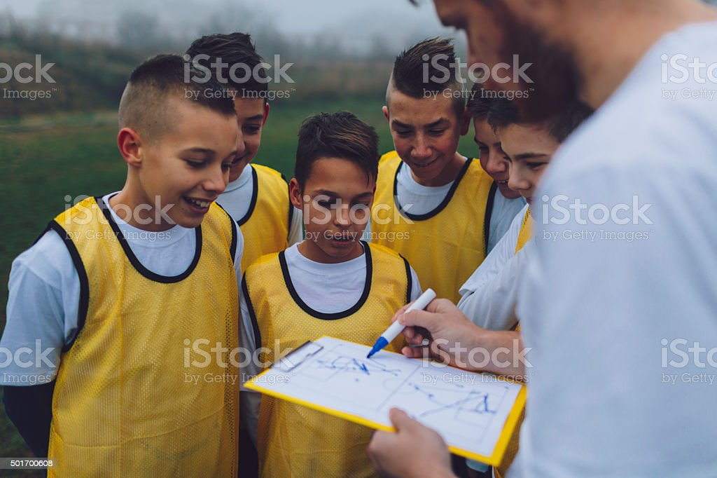 Coach Giving Instruction To His Kids Soccer Team. stock photo