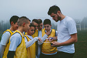 Coach Giving Instruction To His Kids Soccer Team.