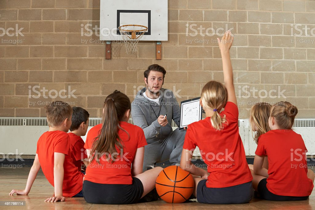 Coach Giving Team Talk To Elementary School Basketball Team stock photo