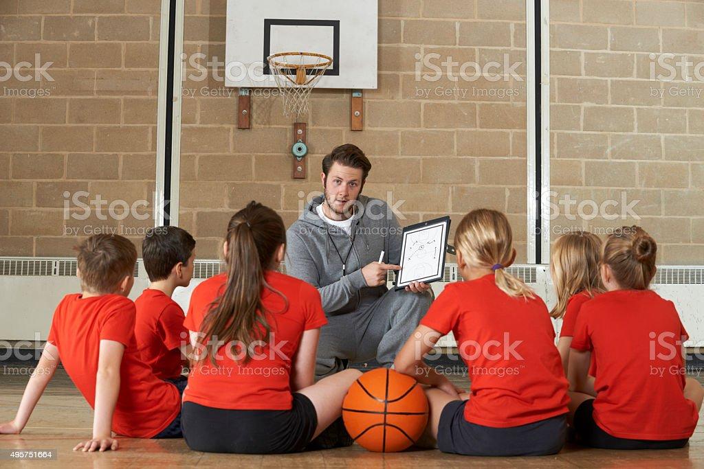 Coach Giving Team Talk To Elementary School Basketball Team stock photo