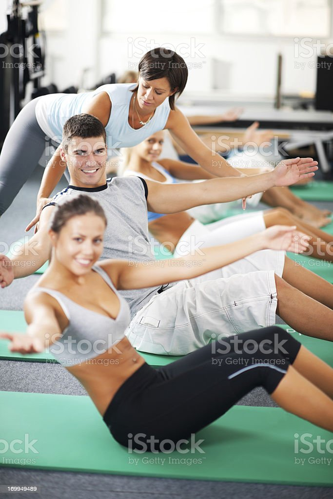 Coach helping people with Pilates exercises royalty-free stock photo