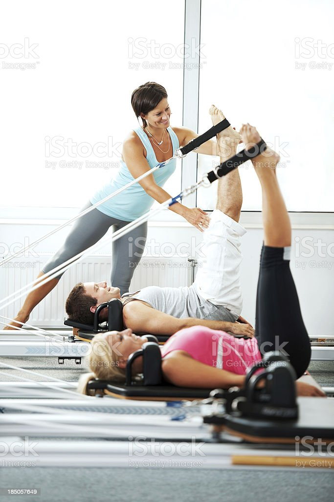 Coach helping people with Pilates exercises. stock photo