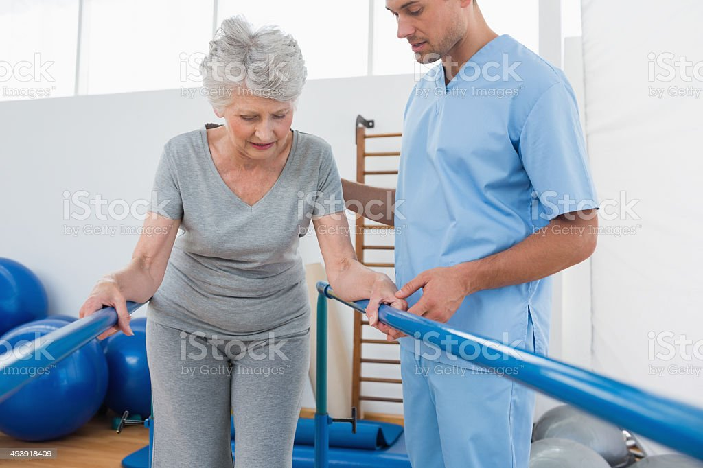 Coach helping senior woman walking on parallel bars stock photo