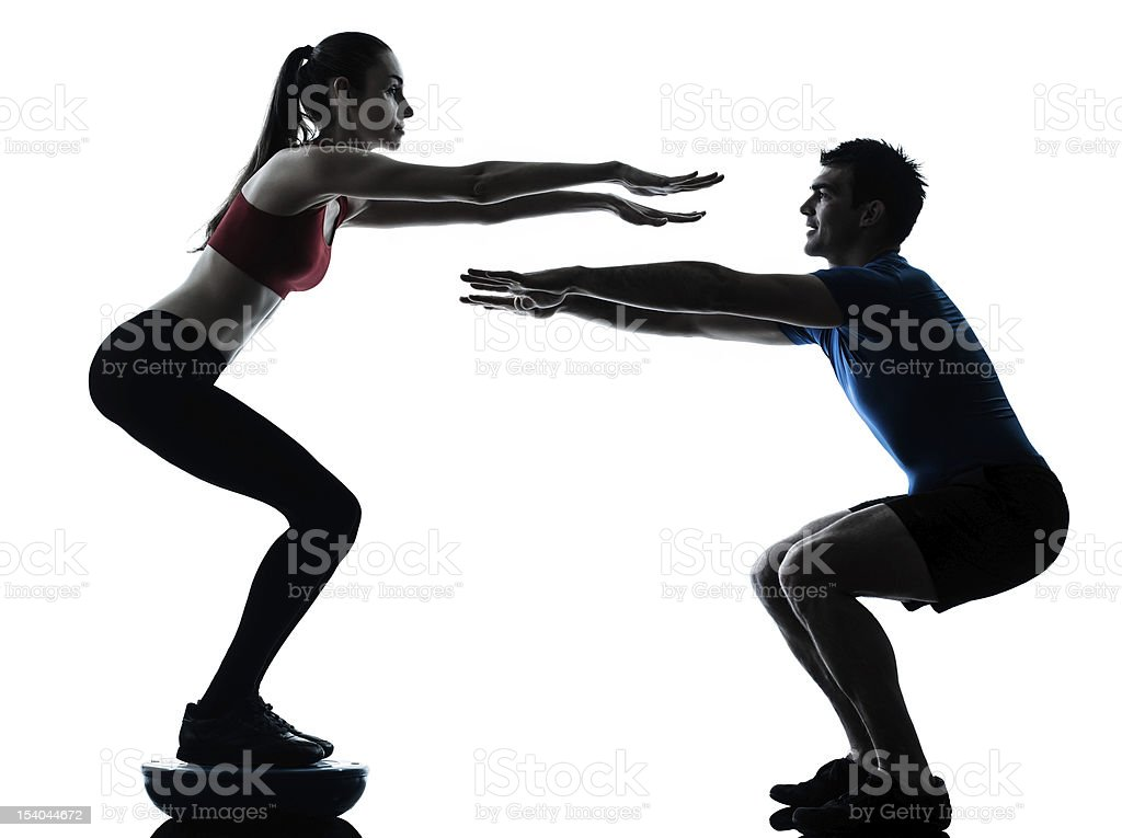 coach man woman exercising squats on bosu royalty-free stock photo