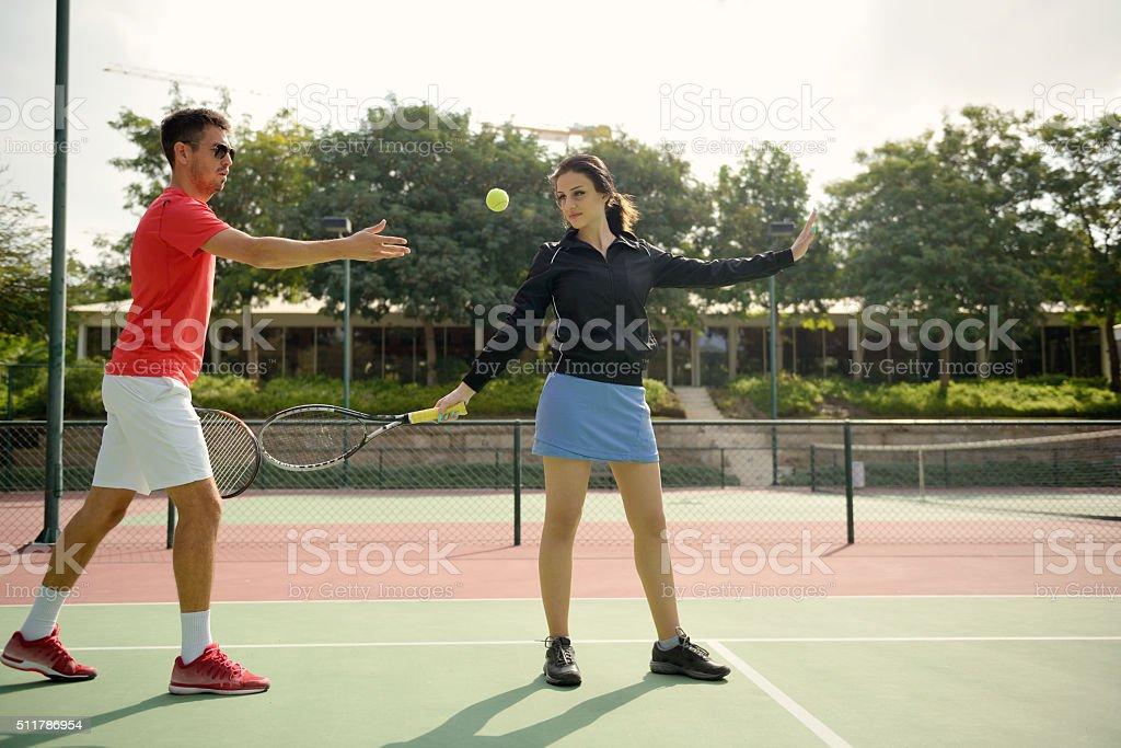Coach teaching tennis to a woman stock photo
