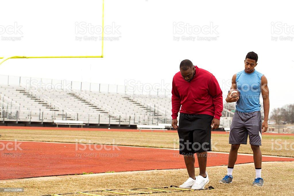 Coach training a high school athlete for football. stock photo