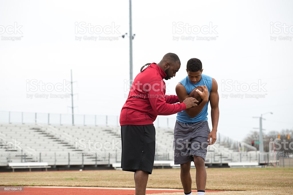 Coach training a high school athlete for football. stock photo