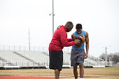 Coach training a high school athlete for football.