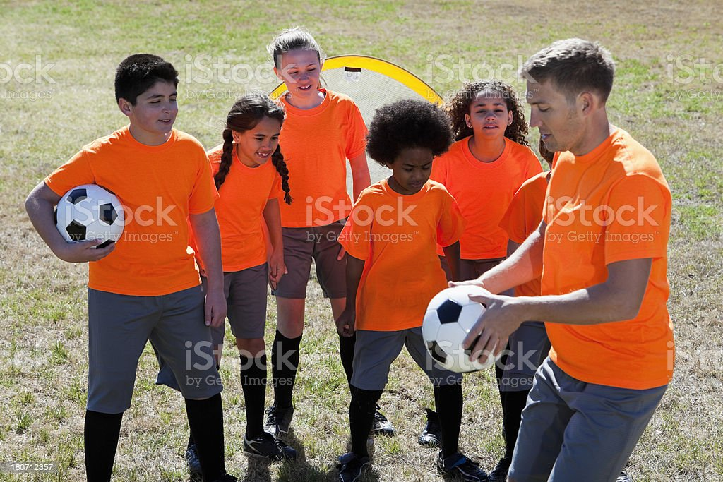 Coach with children practicing soccer royalty-free stock photo