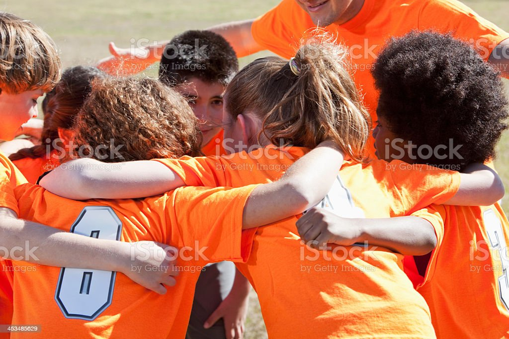 Coach with team of children in sports uniform, in huddle giving pep...
