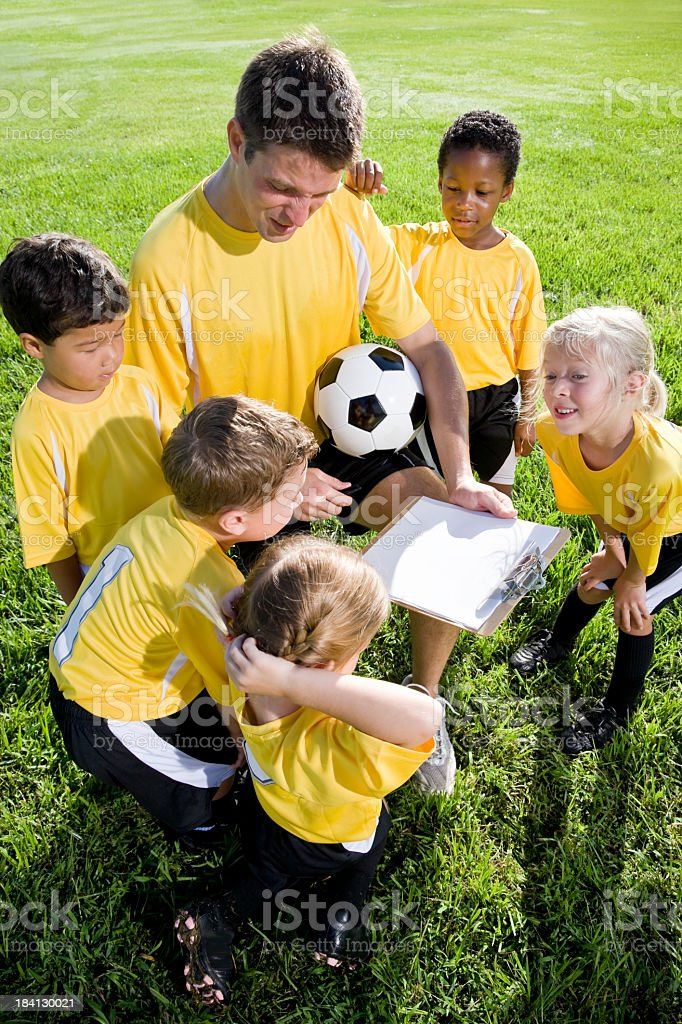 Coach with diverse team of young children playing soccer royalty-free stock photo