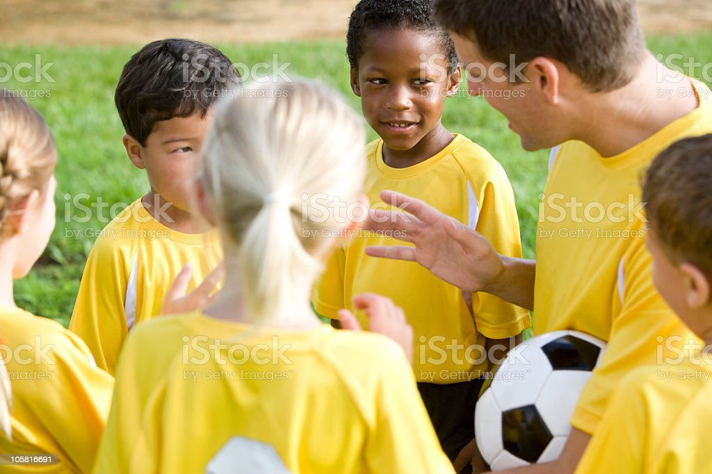 Coach with diverse young team of soccer players royalty-free stock photo