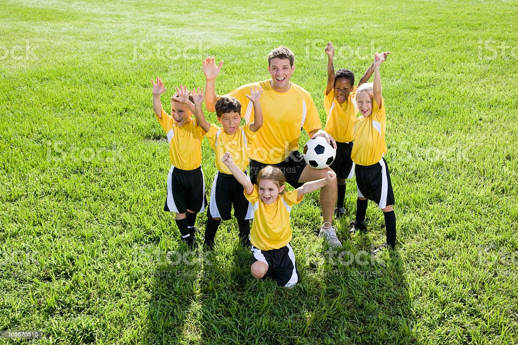 Coach with excited diverse team of young children playing soccer royalty-free stock photo