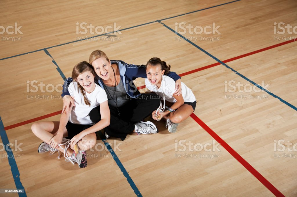 Coach with girls in gym class stock photo