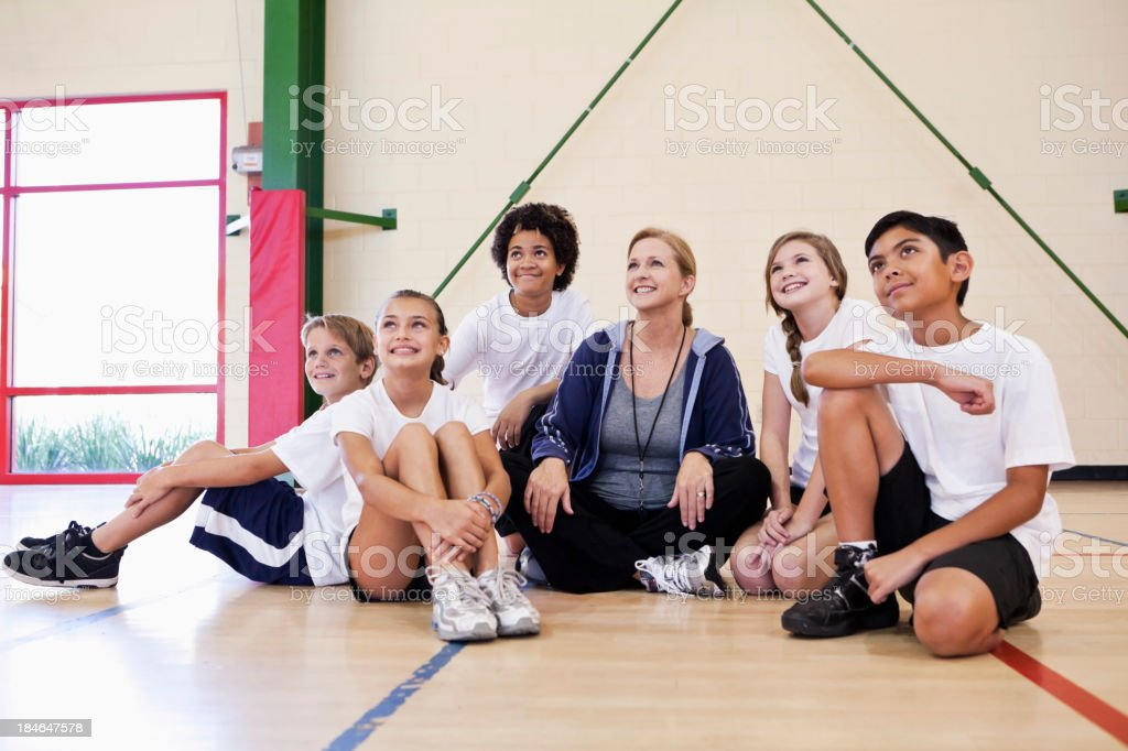 Coach with group of children in phys ed class royalty-free stock photo