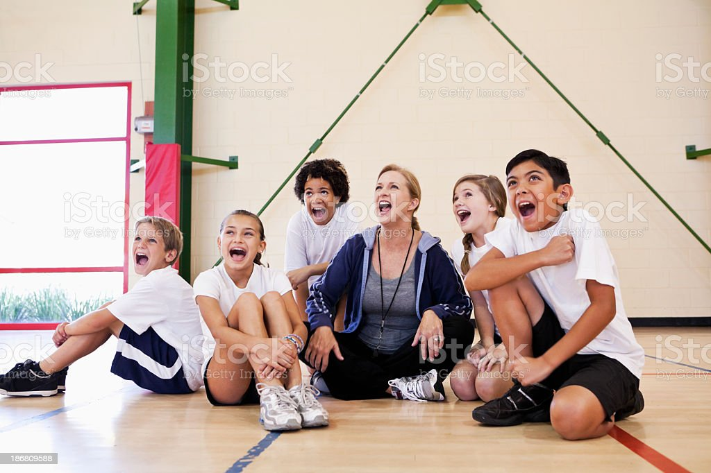 Coach with group of children in phys ed class stock photo