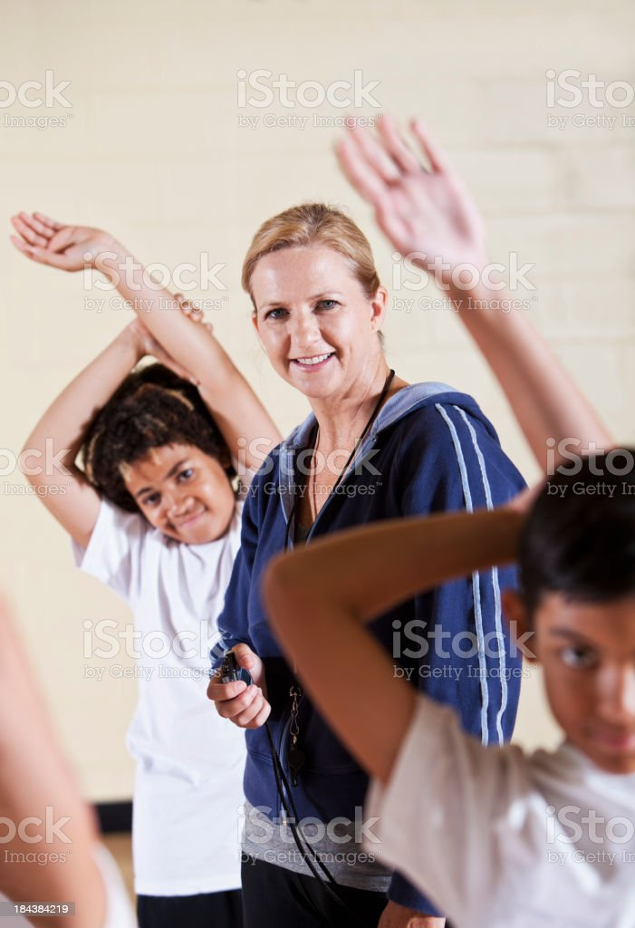 Coach with group of children in phys ed class stretching stock photo