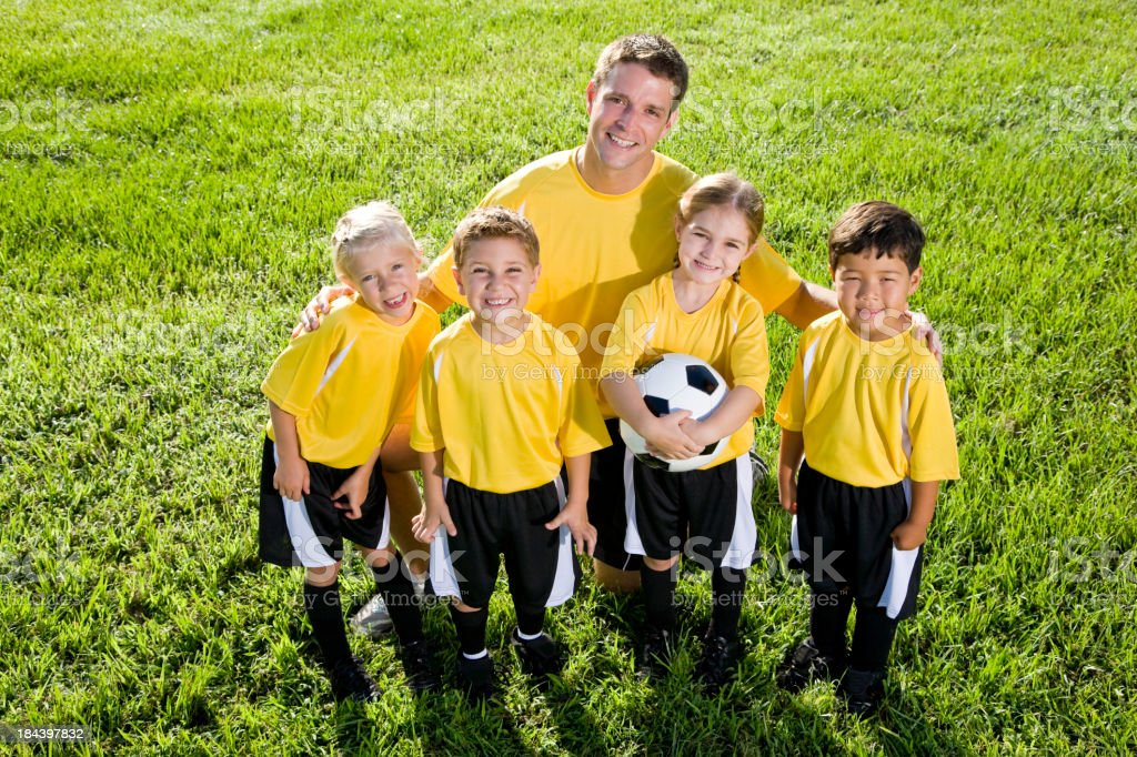 Coach with soccer ball and team of young children royalty-free stock photo