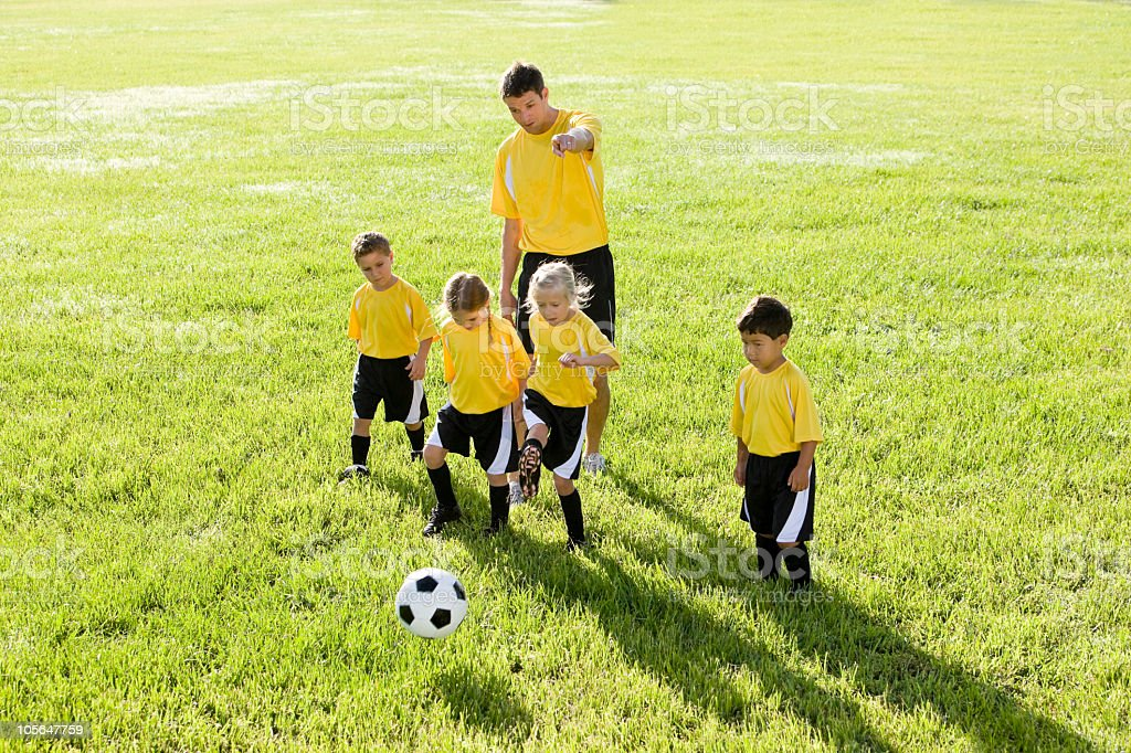 Coach with team of children playing soccer royalty-free stock photo