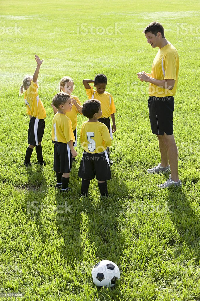 Coach with team of young children playing soccer royalty-free stock photo