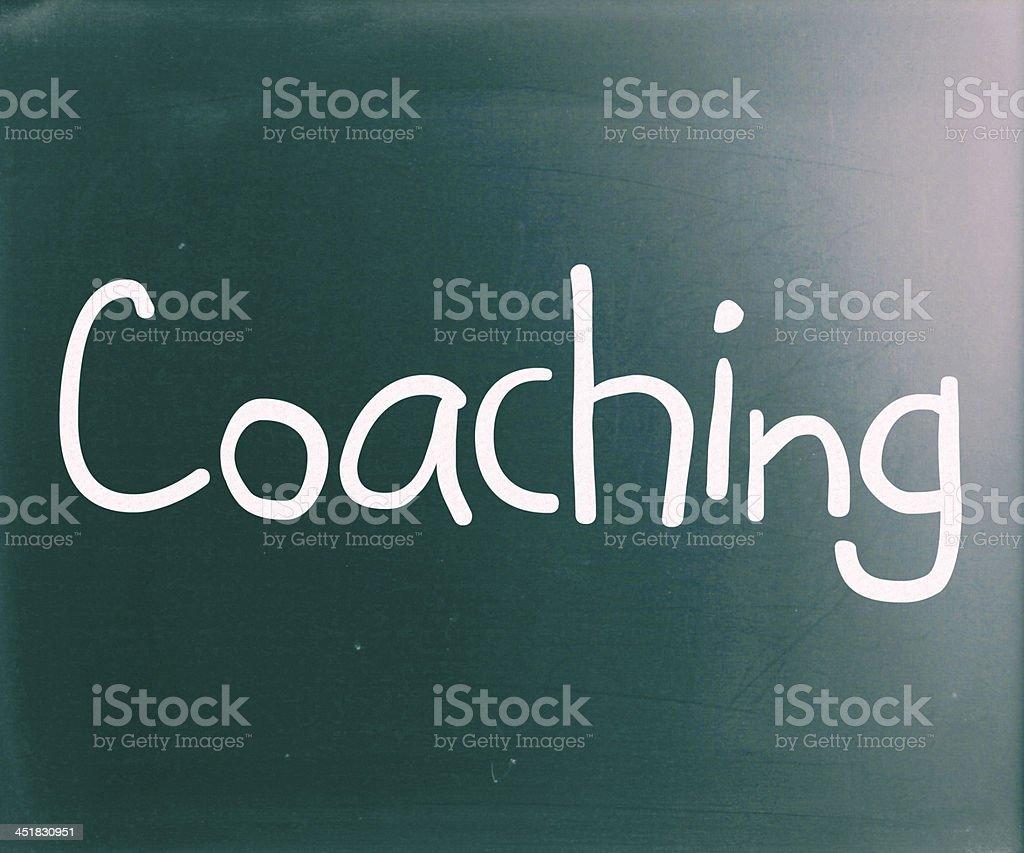 'Coaching' handwritten with white chalk on a blackboard stock photo