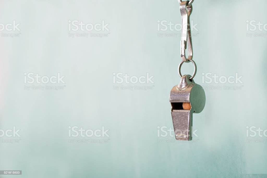 Coach's whistle hangs in front of green school chalkboard. stock photo