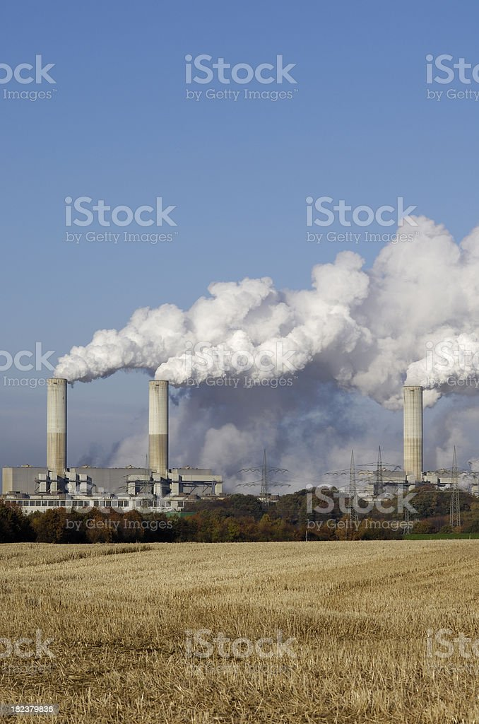 Coal burning power plant and stubble field royalty-free stock photo