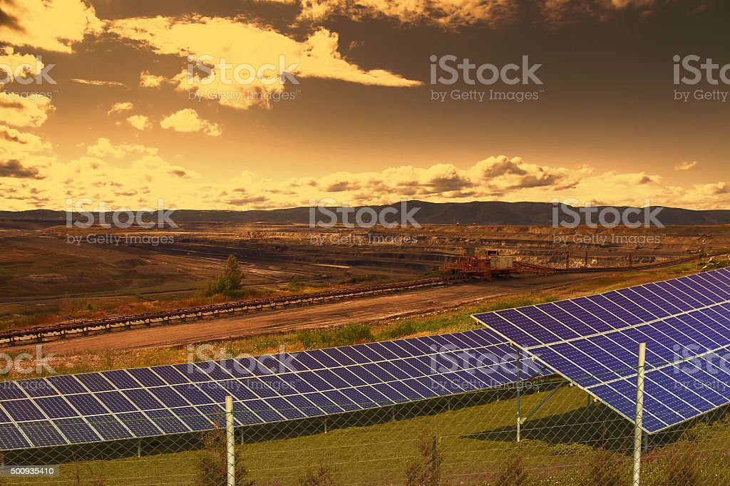 Coal mine with solar energy panels at sunset stock photo