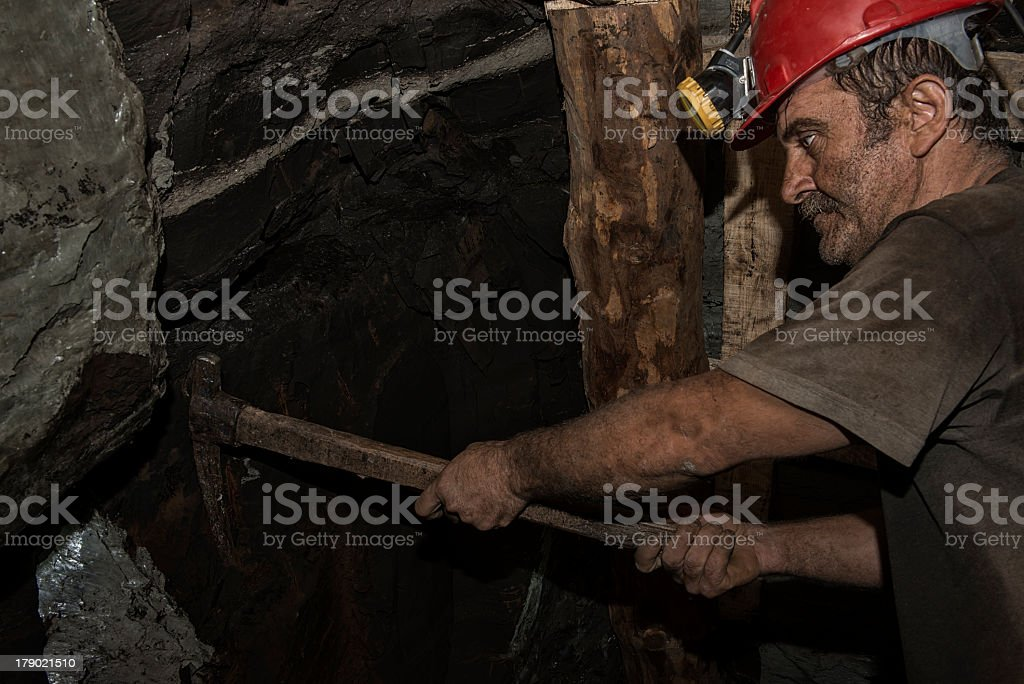 Coal miner working with a pick down a mine stock photo
