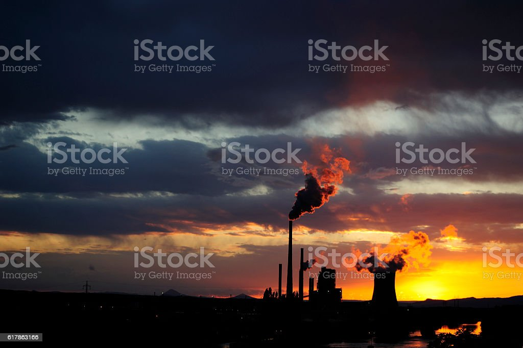 Coal power station with smoking chimneys in sunset stock photo