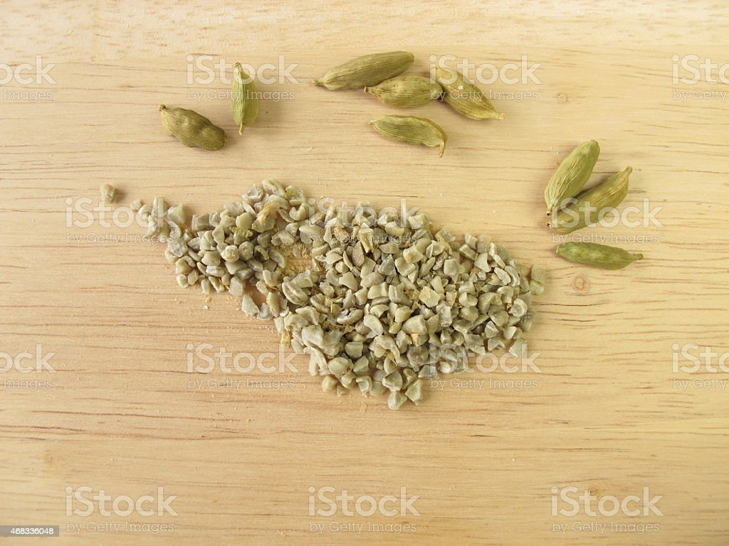 Coarsely ground green coffee beans and cardamom stock photo
