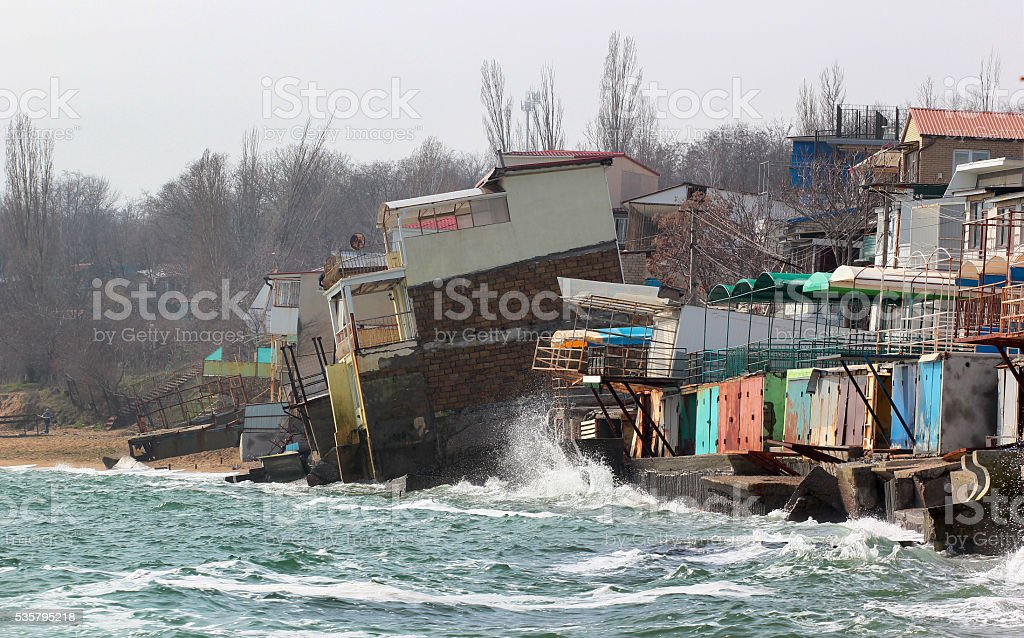 Coastal erosion, houses slide down to sea stock photo