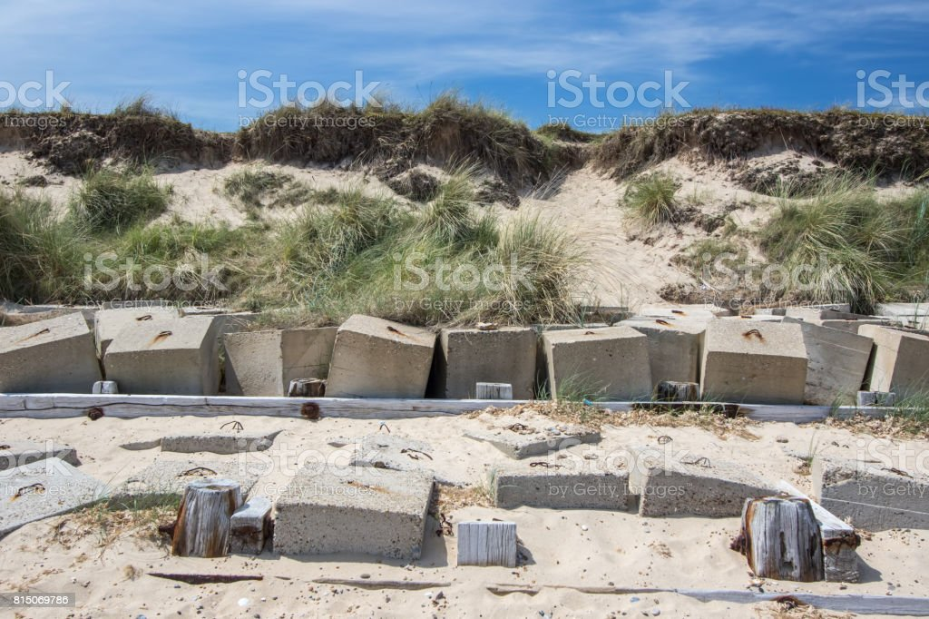 Coastal erosion management with concrete blocks. Sea defenses in front of cliffs. stock photo