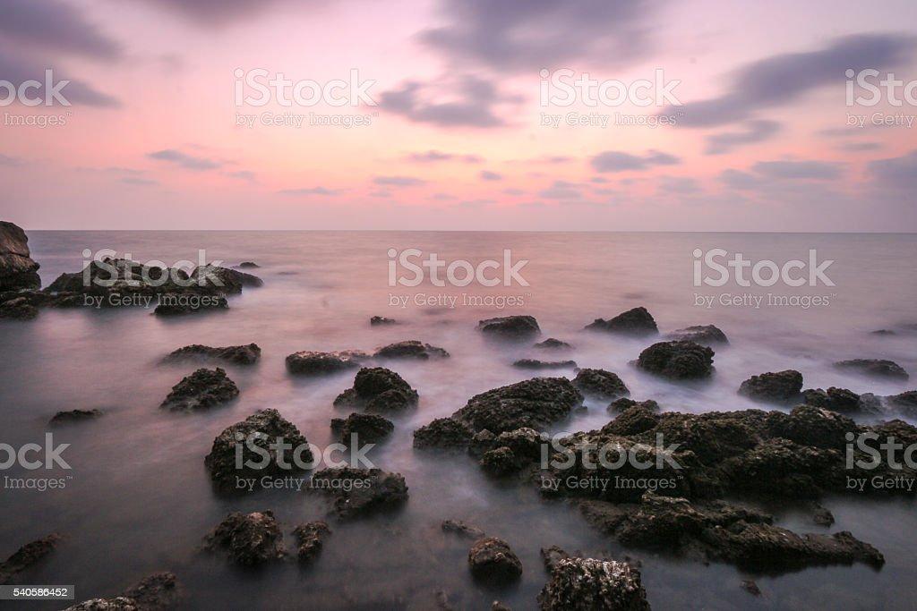 Coastal twilight scene, Long Exposure of rocks and sea waves stock photo