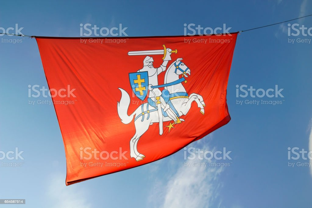 Coat of arms of the Republic of Lithuania on the red flag against the sky .  Emblem approved by national referendum in 1992 stock photo