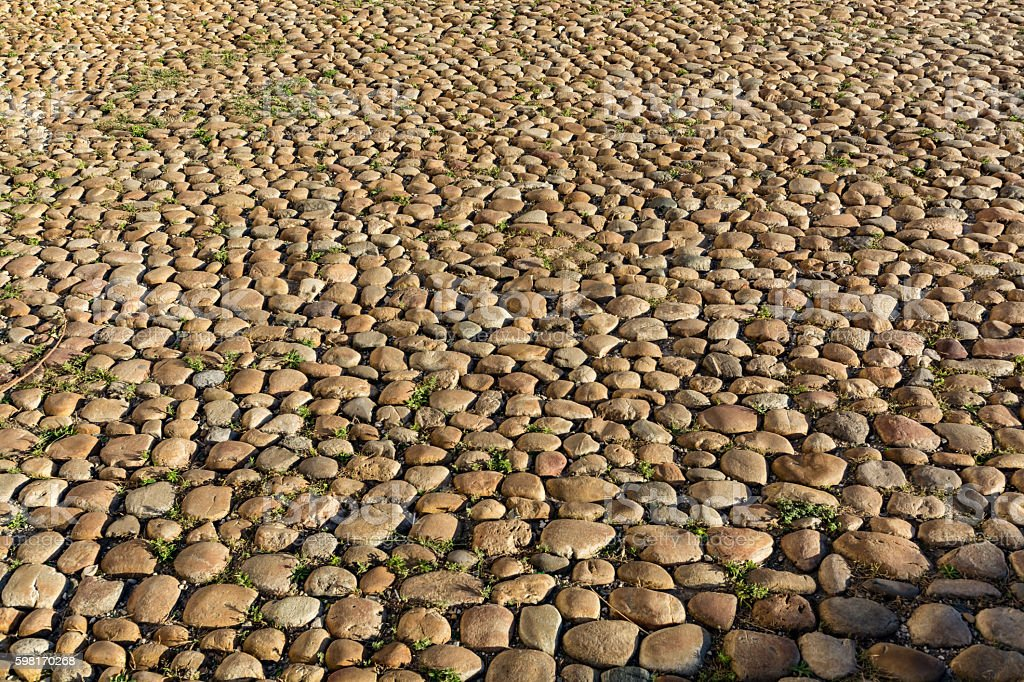 Cobbled, ancient stone road background stock photo