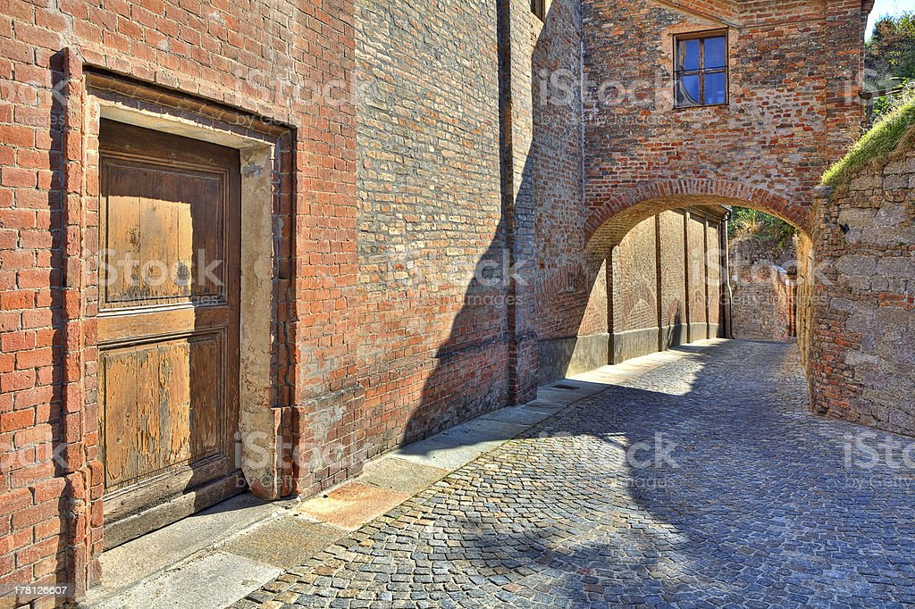 Cobbled street and red brick wall in italian town. royalty-free stock photo