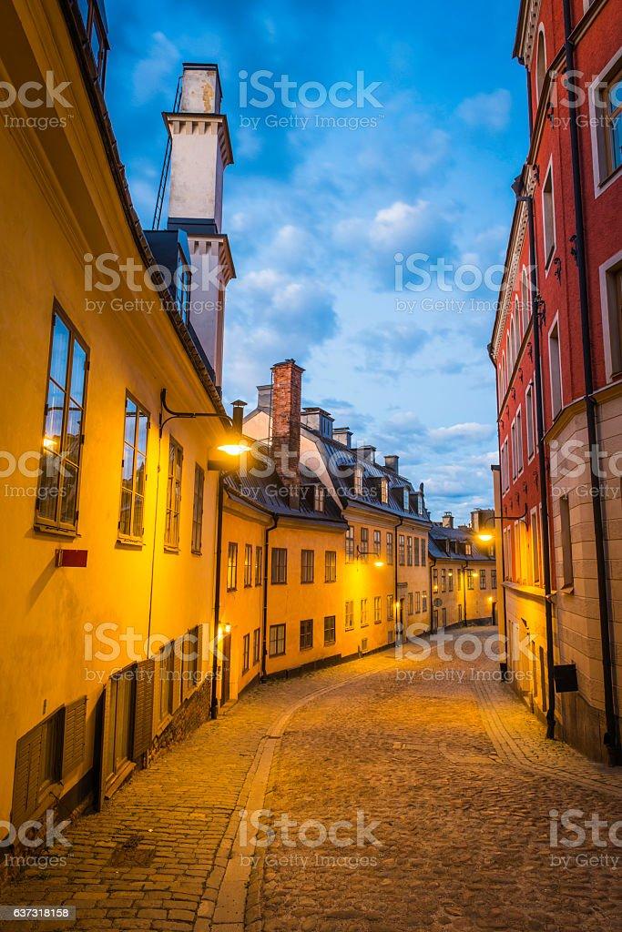 Cobbled street through warmly illuminated townhouses at dusk Stockholm Sweden stock photo